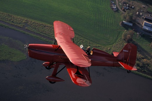 Red Bi-wing Plane Flying Over Water And Farms : Stock Photo