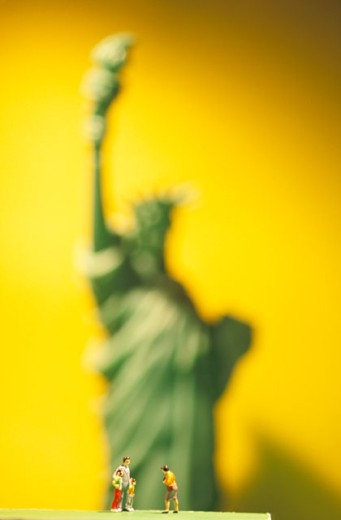 Toy People In Front of Toy Statue of Liberty : Stock Photo