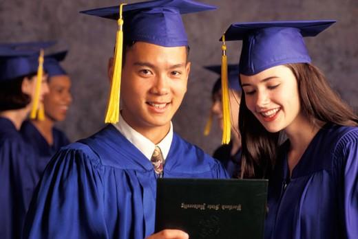 Graduates Looking At Diploma And Smiling : Stock Photo