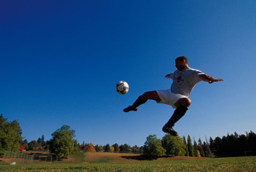 Stock Photo: 1525R-45620 Man Kicking Soccer Ball in Mid Air