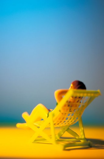 Toy Person Sunbathing : Stock Photo
