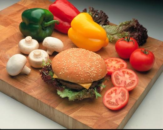 a burger on a bun with salad/vegetable items : Stock Photo