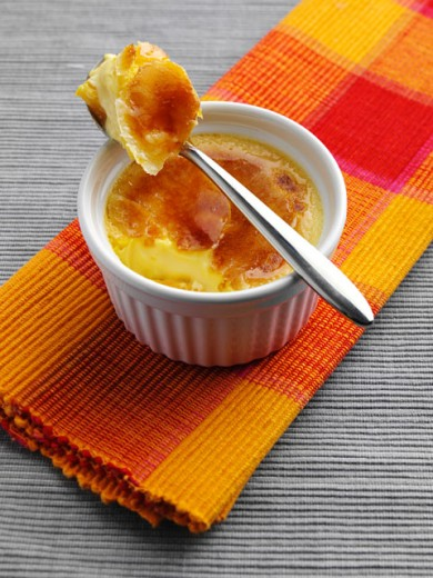 High angle view of a bowl of creme brulee with a spoon : Stock Photo