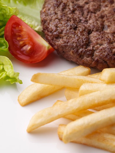 Close-up of a burger patty with French fries and salad : Stock Photo