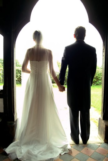 Rear view of a young bride and groom holding hands in a doorway : Stock Photo