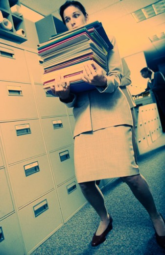 Low angle view of a businesswoman carrying a stack of files : Stock Photo