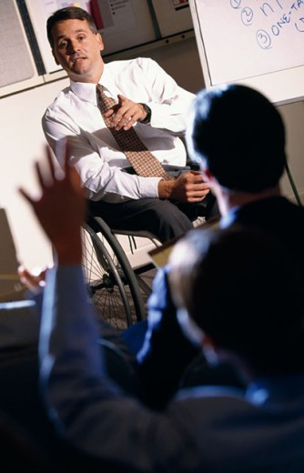 Businessman giving a presentation to his colleagues : Stock Photo