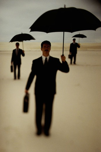 Silhouette of three businessmen holding umbrellas in a desert : Stock Photo