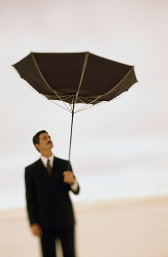 Businessman holding an umbrella in a desert : Stock Photo