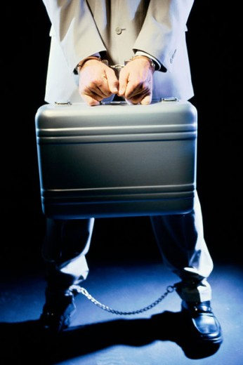 Low section view of a businessman holding a briefcase with handcuffs : Stock Photo