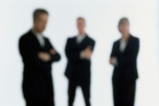 Stock Photo: 1525R-78076 Businesswoman and two businessmen standing with their arms crossed