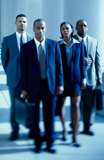 Three businessmen and a businesswoman walking in a corridor : Stock Photo