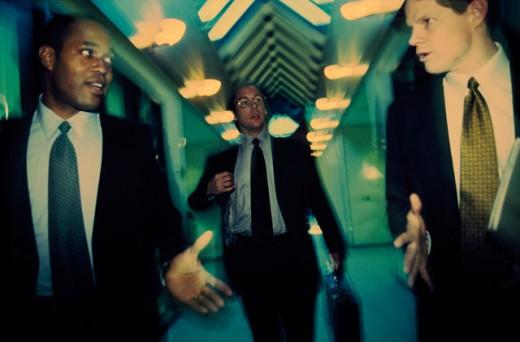Stock Photo: 1525R-78228B Three businessmen walking in a corridor