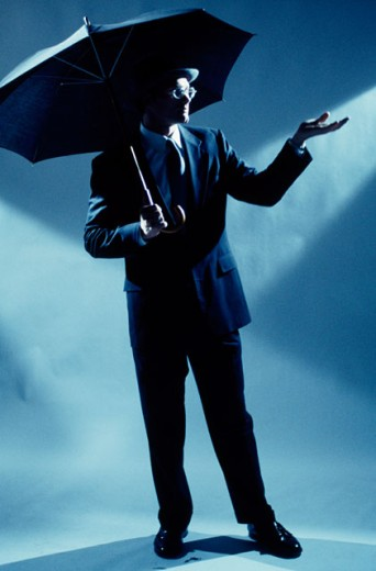 Businessman holding an umbrella : Stock Photo