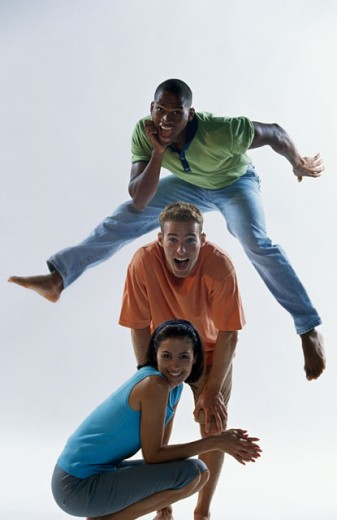 Portrait of two young men and a young woman posing : Stock Photo