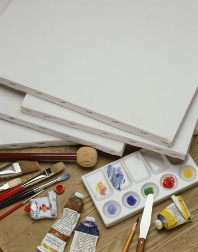 High angle view of a palette with paintbrushes and canvas : Stock Photo