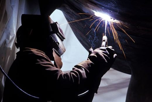 Side profile of a welder working with a welding torch : Stock Photo