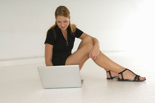 Stock Photo: 1525R-80920 Young woman using a laptop and smiling