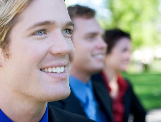 Three businesspeople standing together looking ahead and smiling : Stock Photo