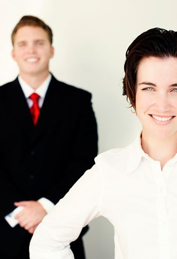 Business man in black suit and tie stands behind smiling woman in white clothes : Stock Photo