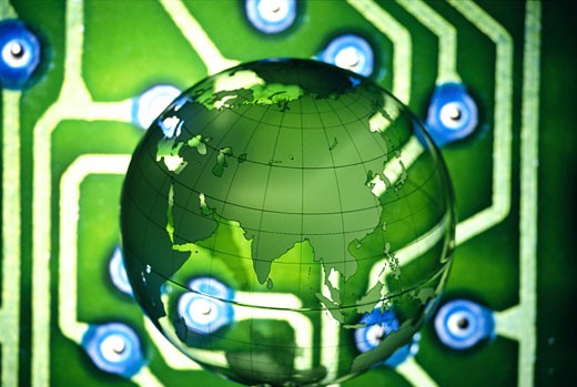 Close-up of a globe superimposed over a circuit board : Stock Photo