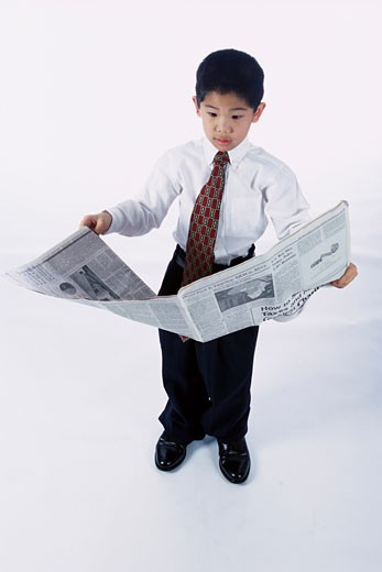 Portrait of a young boy dressed as a businessman reading a newspaper : Stock Photo
