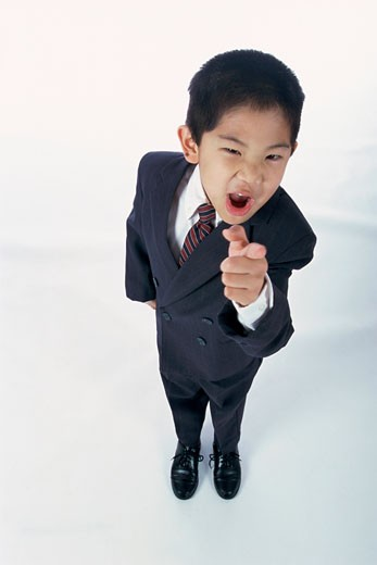 Portrait of a young boy dressed as a businessman pointing : Stock Photo