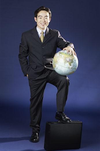 Portrait of a businessman holding a globe : Stock Photo