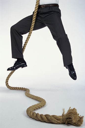 Stock Photo: 1525R-81859 Low section view of a man climbing a rope