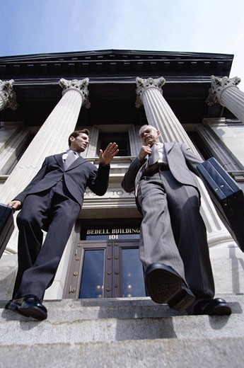 Stock Photo: 1525R-82239 Low angle view of two businessmen walking down stairs