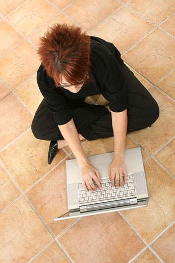 Stock Photo: 1525R-82437 High angle view of a businesswoman sitting on the floor and working on a laptop