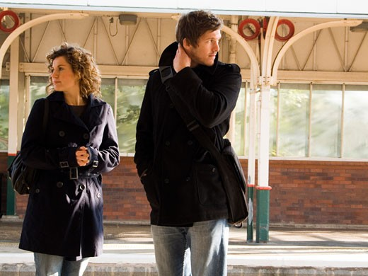 Young couple standing at a railroad station platform : Stock Photo
