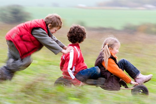 Boy and girl riding a mountain board with a boy pushing them from behind : Stock Photo