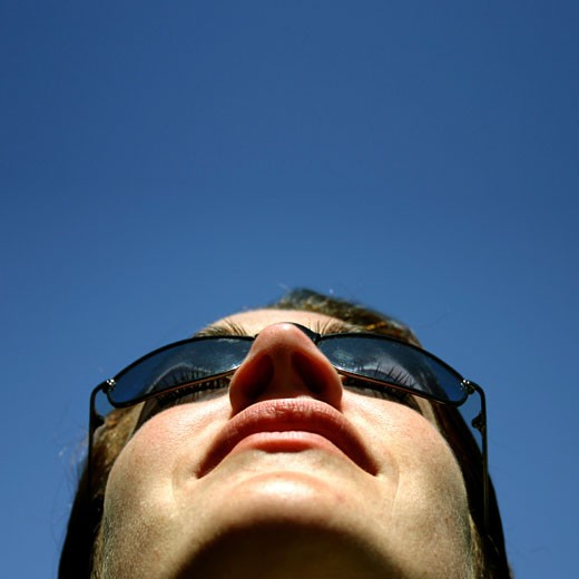Stock Photo: 1525R-88686 Business woman looks up intot the blue sky with her sunglasses