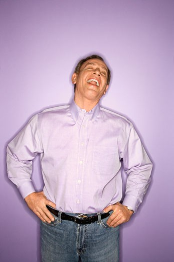 Laughing middle-aged Caucasian man wearing purple clothing on purple background. : Stock Photo