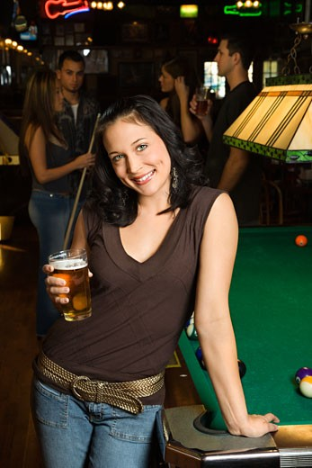 Stock Photo: 1525R-99228 Portrait of young caucasian woman holding beer beside billiards table in pub.