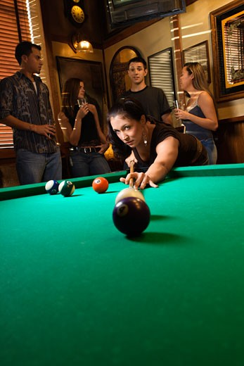 Young caucasian woman preparing to hit pool ball while playing billiards. : Stock Photo