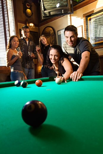 Young caucasian woman receiving advice on shooting pool ball while playing billiards. : Stock Photo