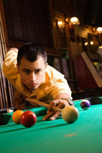 Young man concentrating while aiming at pool ball while playing billiards. : Stock Photo