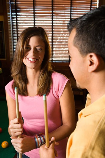 Young man and woman talking and smiling while playing billiards. : Stock Photo