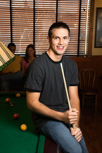 Stock Photo: 1525R-99254 Portrait of young man leaning on billiards table holding pool stick.
