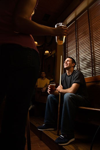 Stock Photo: 1525R-99259 Young man holding billiards cue while hanging out at pub.