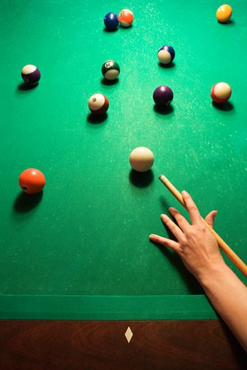 Stock Photo: 1525R-99276 Woman's hand preparing to hit pool ball while playing billiards.