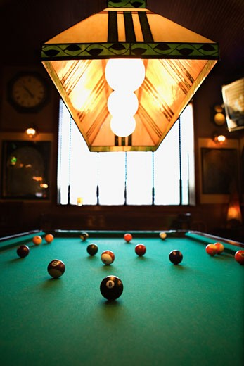 Stock Photo: 1525R-99283 Green billiards table with pool balls spread out.