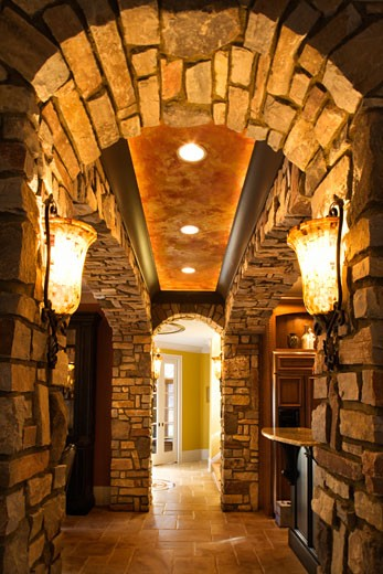 View of foyer through stone archway in affluent home. : Stock Photo