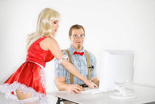 Stock Photo: 1525R-99604 Caucasian young man smiling dressed like nerd sitting at computer looking at viewer with Caucasian young blonde woman in sexy french maid outfit bending over and pointing.