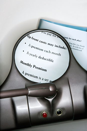 Vision magnifying glass used to view health insurance information. : Stock Photo