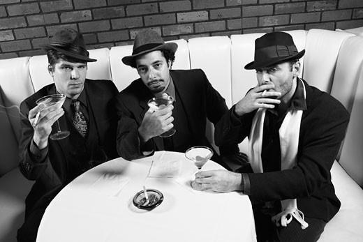 Stock Photo: 1525R-99797 Three Caucasian prime adult males in retro suits sitting at table with cocktails looking at viewer.