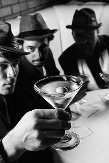 Stock Photo: 1525R-99802 Three Caucasian prime adult males in retro suits sitting at table with martini.