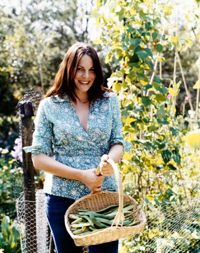 Smiling Woman Stands in a Vegetable Garden Holding a Basket of Broad Beans : Stock Photo